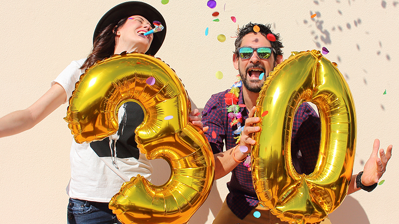 Cheerful couple celebrating with 30-shaped balloons