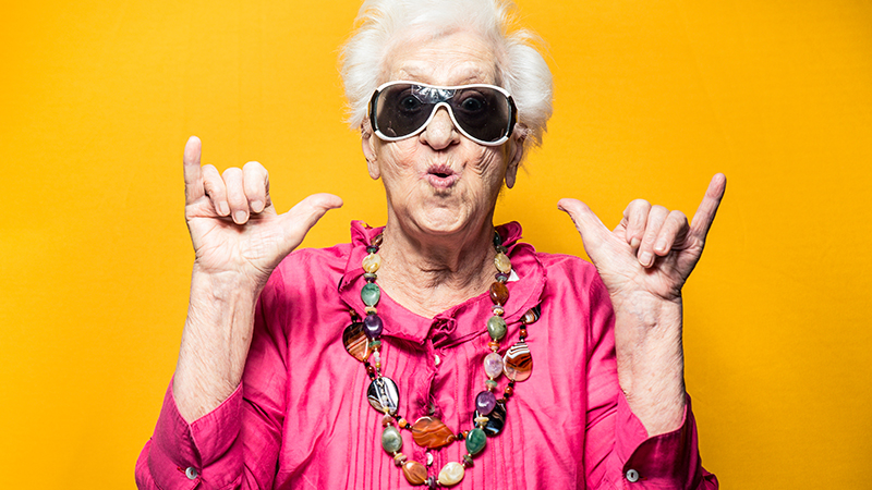 Colourful older lady with sunglasses doing the shaka gesture with both hands