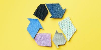 Pieces of fabric arranged in the shape of the recycling symbol