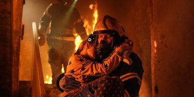 A firefighter carrying a child down a staircase from a burning house