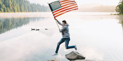 Man jumping with US flag over river