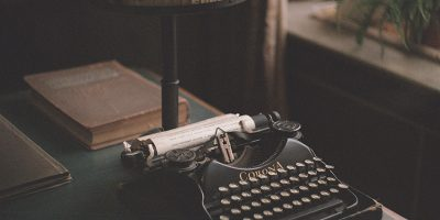 A worn Corona typewriter standing on a desk next to a window, surrounded by old books and a vintage lamp