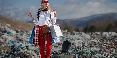 Woman with shopping bags standing in a landfill