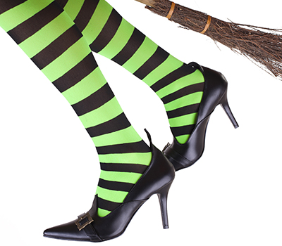 Green and black striped legs of a witch flying on her broomstick