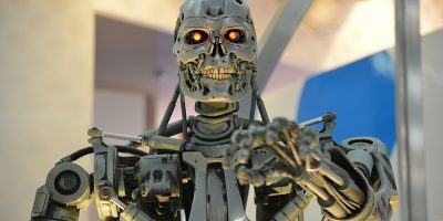 """A metallic robot skeleton with teeth and red lights for eyes, reaching towards the camera (T800 from the movie """"Terminator"""")"""