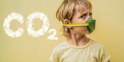 """Boy in leaf mask looking away from smoke text that says """"CO2"""""""