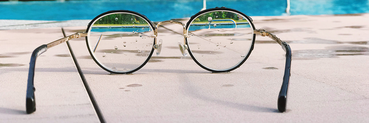 Glasses lying on the ground next to a pool, rendering an otherwise blurry image clear