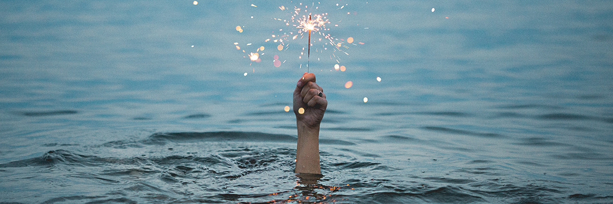 Hand sticking out of the water, holding a lit sparkler